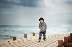 Stylish boy in a hat standing on a wooden bridge on the background of the sea