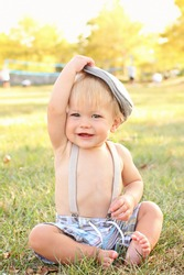 Baby, toddler boy wearing suspenders and a country / newsboy hat, outdoors, featuring seasonal, fall colors, suitable for Thanksgiving or Halloween or Fall theme