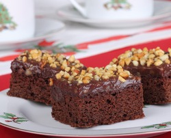 Christmas plate of fudge brownies topped with chocolate icing and nuts
