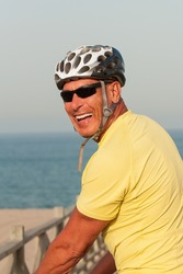 Portrait of a happy smiling active older man with a cycling helmet on a summer evening