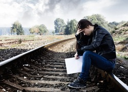 Lonely teenage girl with letter sitting on the railroad.