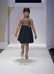 NEW YORK - OCTOBER 21: Girl walks runway petite Parade show by Lamantine Paris during kids fashion week sponsored by Vogue Bambini & Swarovski Elements at Industria Supertudio on Oct 21, 2012 in NYC