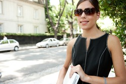 Portrait of an attractive young businesswoman holding a laptop computer under her arm and wearing shades while in a leafy street in the city with classic architecture.