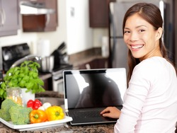 Woman using laptop computer in kitchen with greens and vegetables. Lifestyle cooking concept with smiling happy mixed-race Asian chinese Caucasian woman working sitting in her kitchen.