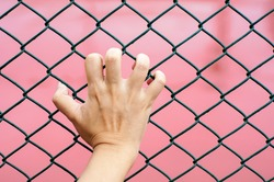hand holding on chain link fence, red background