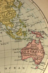 Macro of an old atlas map (about 100 years old) of Australasia and South-east Asia, on yellowing, slightly stained paper.