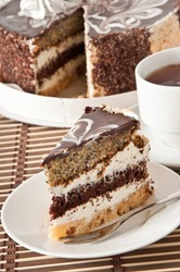 Close up of homemade chocolate cake in white plate and tea