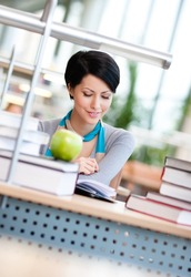 Female student with green apple studies at the reading hall of the library. Process of education