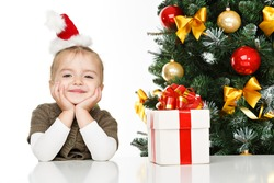 Happy little girl smiling with gift box near the Christmas tree. Christmas concept.
