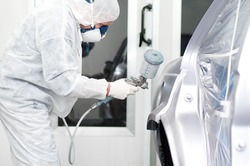 worker painting a car in a special painting box, wearing a white costume
