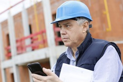 Entrepreneur on construction site using smartphone