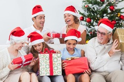 Excited family exchanging gifts at christmas on the couch