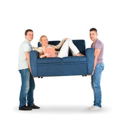 Two men carrying a couch with a woman smiling