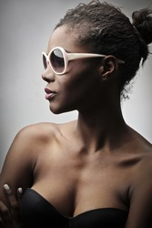 Beautiful black girl, with a pair of white sunglasses, posing