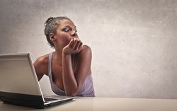 A beautiful black girl, while is using a laptop computer, thinks