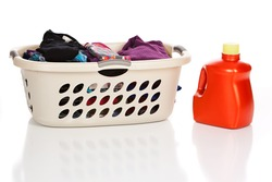 Laundry basket with clean, folded clothes and a bottle of Laundry Detergent isolated on white.