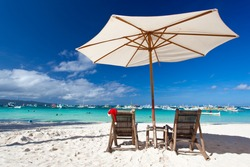Sun umbrella with Santa Hat on chair longue on tropical beach
