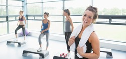 Happy woman taking break at aerobics class in gym