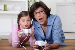 Mother playing vide-games with daughter