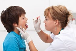 Doctor taking saliva sample from little boy - childhood infectious diseases