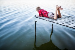 Boy laying on a dock by a lake