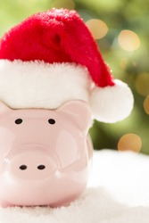 Pink Piggy Bank Wearing Red and White Santa Hat on Snowflakes with Abstract Green and Golden Background.