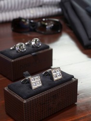 Display of men's diamond and silver cufflinks, DOF focus on cufflinks