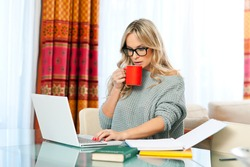 attractive woman with cup of coffee, book and laptop sitting at her home desk and working