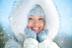 Portrait of young woman in white fur in winter