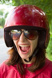 Young scared woman in motorcycle helmet and glasses