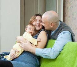 Smiling parents with newborn in home interior
