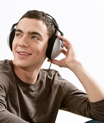 Attractive young man listening to music with his headphones while sitting down, isolated against a white background.