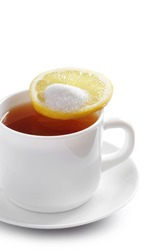 Tea with lemon in the white cup on a white background