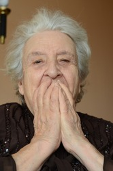 Afraid elderly woman looking to camera in surprise