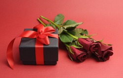 Happy Valentines Day black box with red ribbon gift and red roses, against a red background.
