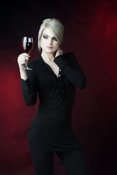 female fashion model,blond hair holding glass of rose wine