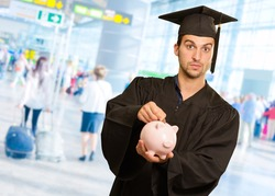 Graduate Man Inserting Coin In Piggy bank, Indoor