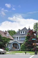 Suburban Gable Front Style Home Residential Neighborhood Sunny Blue Sky Clouds Street