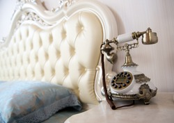 Luxury bedroom interior with vintage telephone on table.