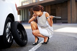 Woman calling for assistance with flat tire on car in the city