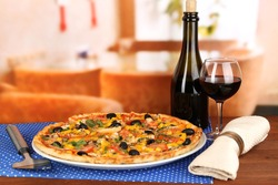 Tasty pizza with wine on wooden table on room background close-up