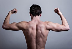 Muscular male back over gray background