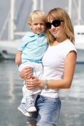 Young white blonde woman holding her little blond son in hands outdoor.Happy family walking on waterfront with yachts on background.Young adult woman holding child.Happy mother with cute kid in summer