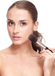 Young beautiful woman applying makeup on face by brush