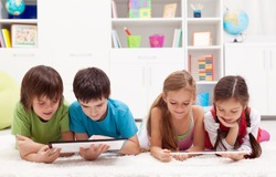 Kids using modern tablet computers laying on the floor
