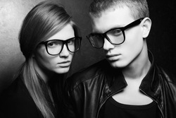 Portrait of gorgeous red-haired fashion twins in black clothes wearing trendy glasses and posing over metal background. Perfect hair and skin. Natural make-up. Hipster style. Studio shot.
