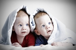 Beautiful redheaded twin babies under blanket