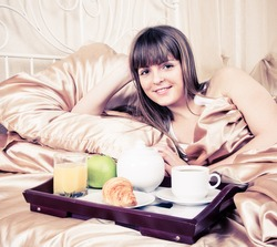 Woman eating breakfast and drinking coffee in bed. Young woman smiling looking at camera