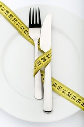 Fork and knife wrapped in measuring tape with copy space