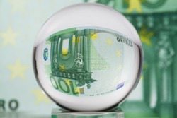 Hundred euro banknote through glass sphere. Blur background.